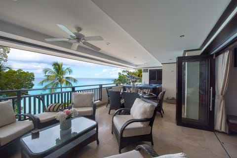Balcony with sea view at Coral Cove 12. Armchairs, dining area, hot tub.