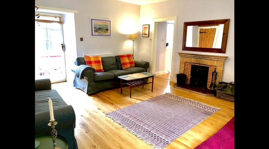 Spacious living room with two couches (one is a pull-out), wood burner, flat screen TV (with Amazon Firestick + an array of videos and DVDs), cupboard full of books & games and door through to conservatory space.