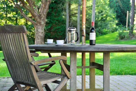 Bottle of red wine and cafettiere of coffee on an outside table in mature gardens