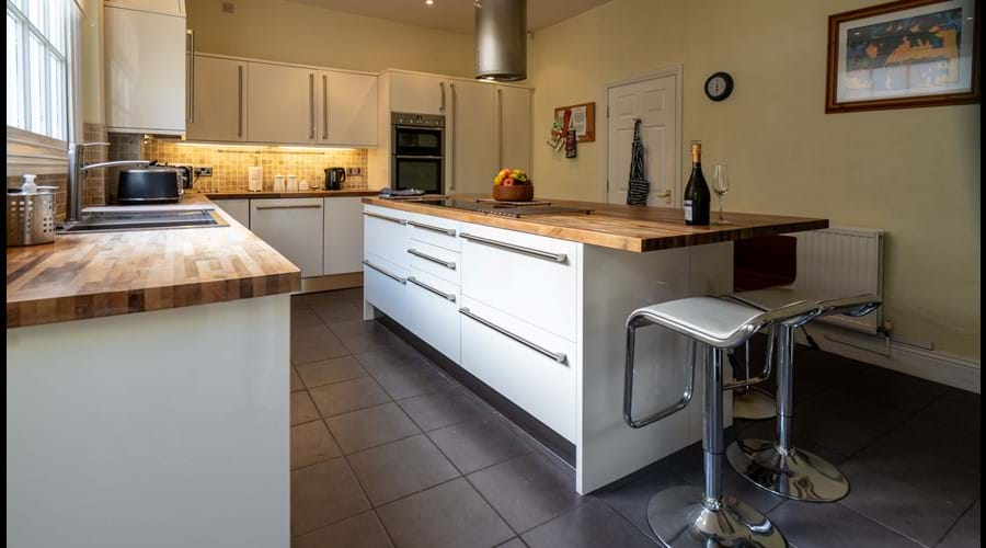 Modern kitchen with large island, barstools, electric hob, double oven, dishwasher, microwave, washer & dryer.