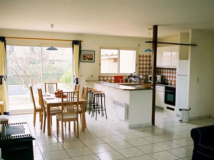 Modern, fully equipped, fitted kitchen with granite topped breakfast bar and the dining area, with patio doors overlooking the terraces, pool and garden.