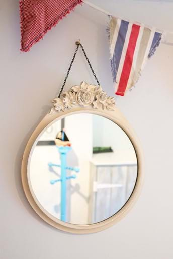 A childrens coat stand is reflected in a bedroom mirror which hangs beneath some bunting in a Devon holiday cottage bedroom