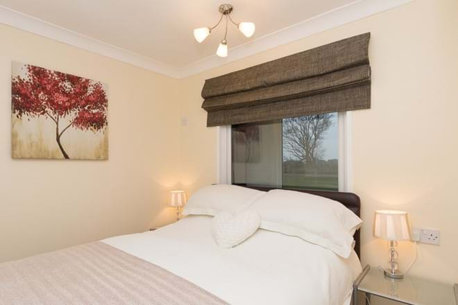 Comfortable double bedroom with open countryside views, side tables, full length mirror and fitted double wardrobe
