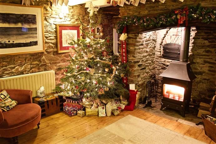 A decorated Christmas tree and inglenook fireplace stand in a Devon Holiday Cottatage lounge