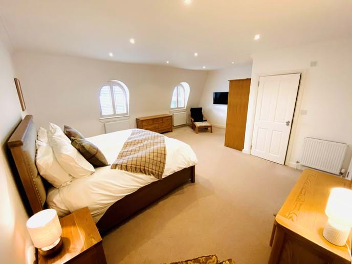 Master bedroom on second floor with sea views, dressing table, large wardrobe, chest of drawers, smart TV and en suite shower room