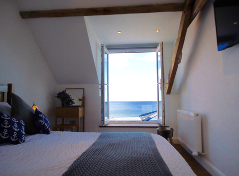 The master bedroom has a king-size bed and a wall-mounted flat-screen TV. The second bedroom has twin beds, and both bedrooms have a fabulous sea view