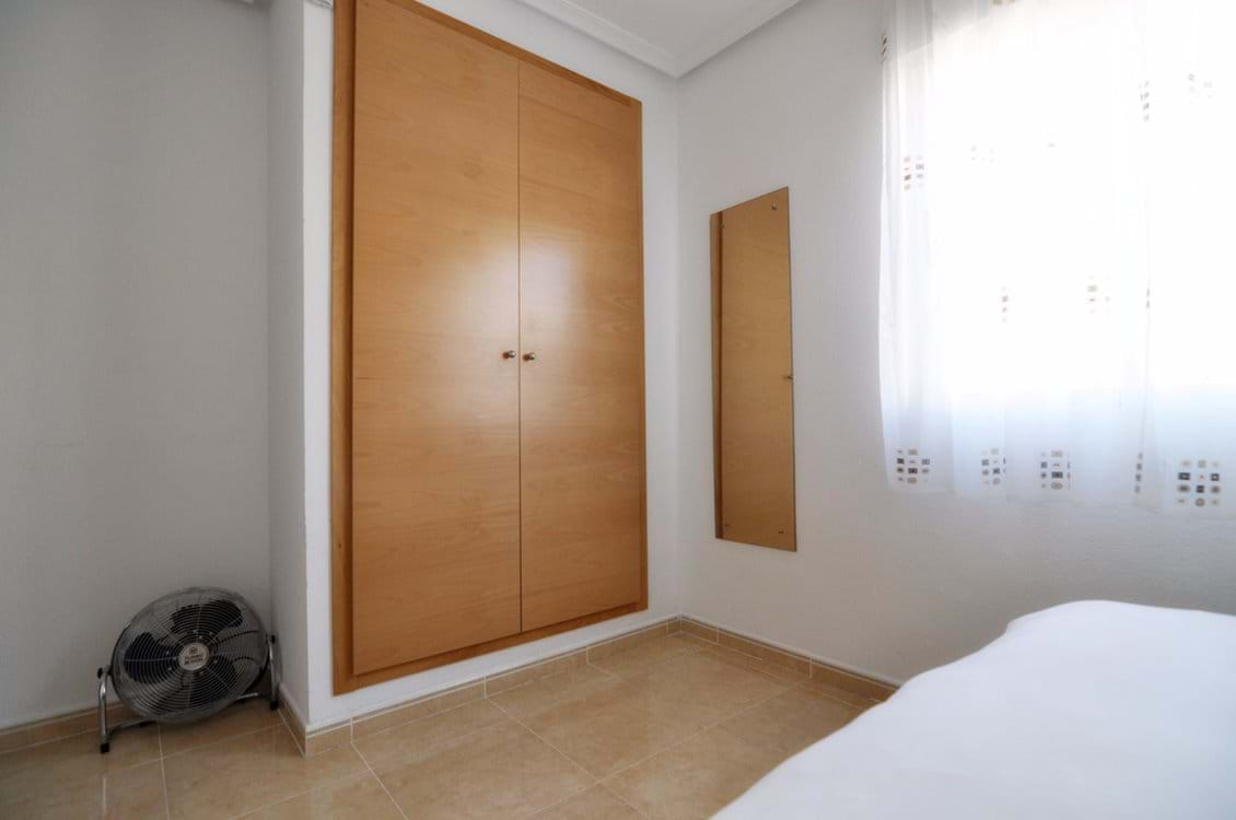 Main bedroom with large fitted wardrobe & storage chests, bedside locker and full-length mirror