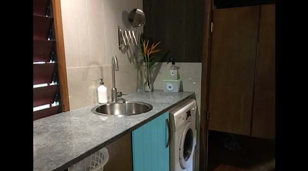 Modern laundry/wet room with 5 kg washing machine & heaps of bench space.