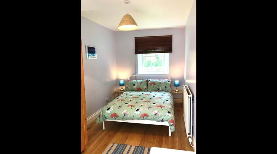 Cosy double room downstairs with sliding glass doors opening onto conservatory.