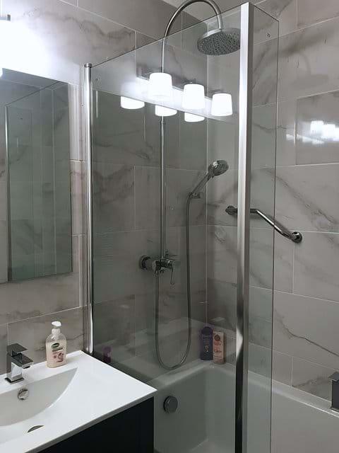 Bathroom has L shaped bath with roomy over bath shower cubicle.
