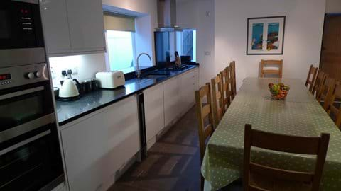 Large kitchen with table seating up to 12 people, double oven, microwave, dishwasher, gas hob