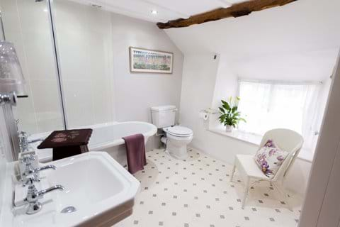 A light and airy bathroom with bath with shower over,sink, WC and a whicker chair
