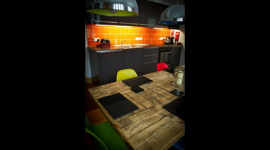Ship Cottage - modern kitchen with low bistro lighting over a reclaimed wood dining table, multi-coloured chairs and coloured tiles