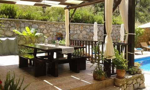 Shaded terrace with outdoor dining table, bbq in background