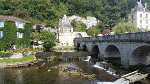 Old bridge spanning river ar Brantome with Abbey behind