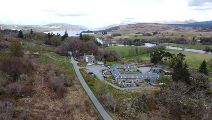 A drone shot of the Steadings development with Loch Rannoch in the background.
