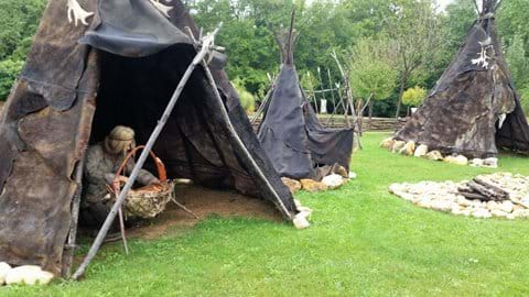 Replica of prehistoric teepees with people cooking