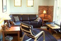 Comfortably furnished and tastefully decorated living room overlooks front deck and waterfront.