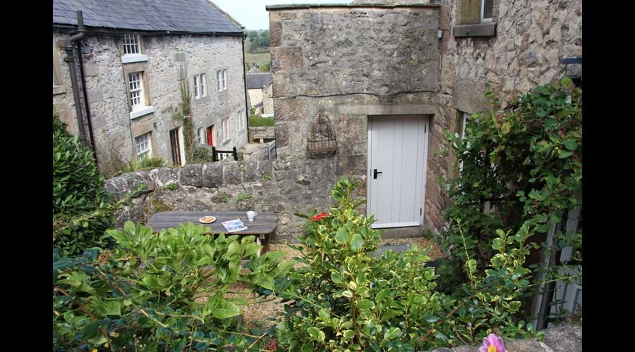 The pretty walled garden has herbaceous plants and a bay tree surrounded by traditional Derbyshire stone walls.