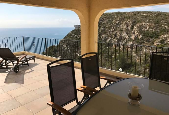 Dining table BBQ and sun loungers on the terrace with sea and mountain views