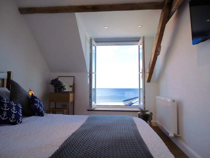 The master bedroom has a king-sized bed and a wall-mounted TV, as well as a stunning panoramic sea view