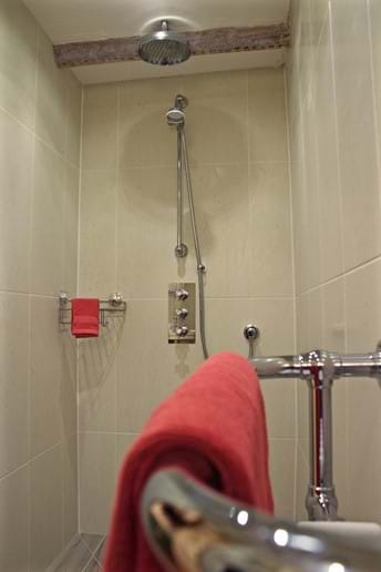Atowel on a heated towel rail with a shower in the background in a Devon holiday cottage
