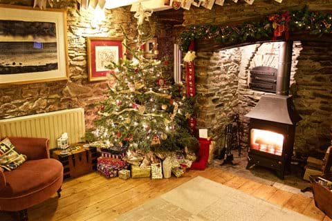 A Christmas tree and presents beside the fireplace in the lounge at Barnfield Cottage
