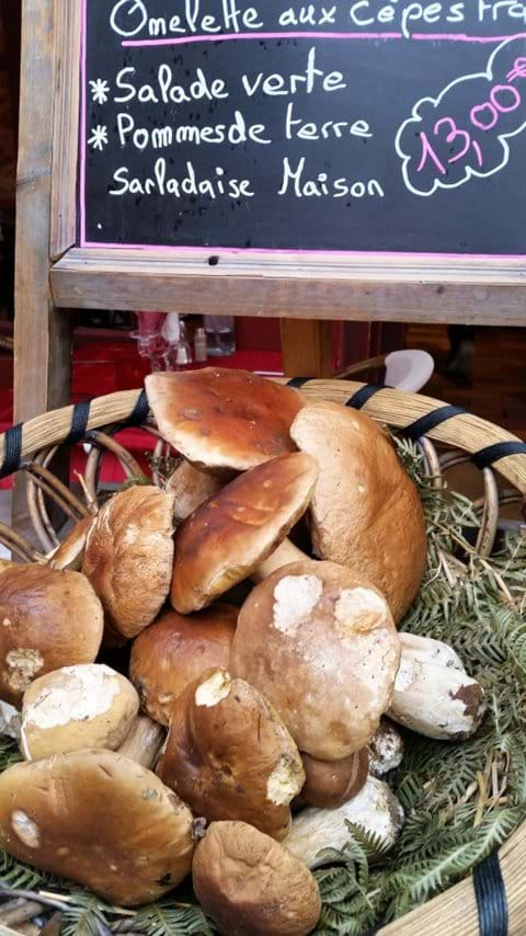 Cepe mushrooms in a basket  with a black board with menu suggestions for 13 euros