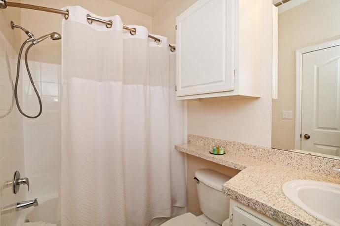 Master Bathroom with shower over bathtub, toilet and washbasin