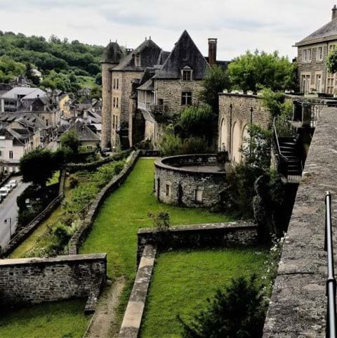 Uzerche town walls and grassy banks with old turreted houses