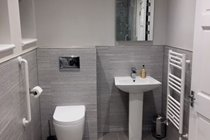 Groundfloor disabled friendly ensuite wetroom with wall hung WC, basin and illuminated mirror