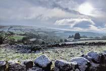 stone wall with snow and countryside views