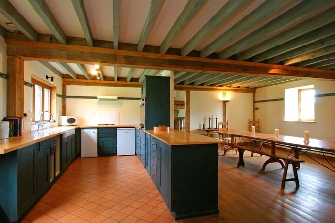 The kitchen in The Barn, Boudet, Normandy which is open plan to the dining area. It's got a fridge, half size dishwasher, oven, gas hob, microwave and plenty of pots and pans to cook and serve with.