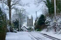 A snowy view up the private lane towards the church in Week St Mary