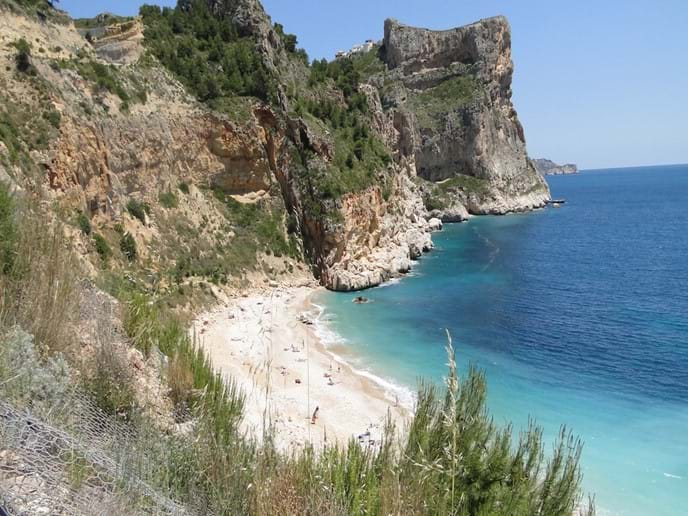 Cala del Moraig beach at Cumbre del Sol, where dramatic cliffs surround the picturesque beach