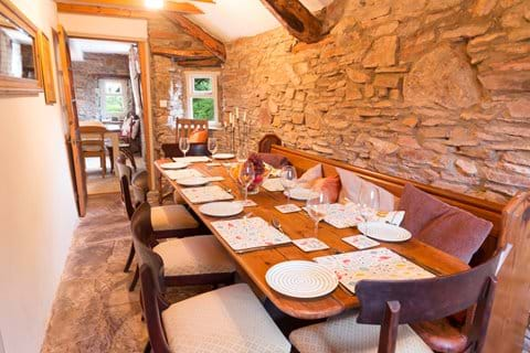 A Devon holiday cottage dining room with a pine table laid for dinner