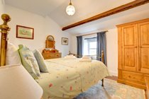 Penny's large bedroom with vaulted and beamed ceiling is fresh, bright and inviting....
