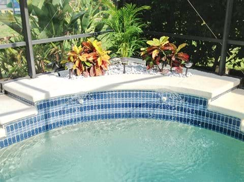 Beautifully landscaped decking and water fountain spraying into the pool