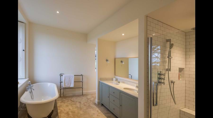 The ensuite to the master bedroom with a Fired Earth roll top bath, double vanity unit and large walk in shower