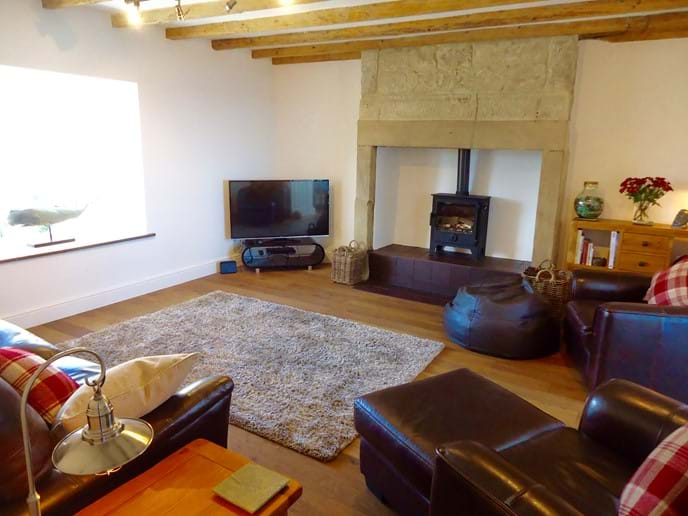 The spacious living room has a large leather sofa and armchairs, a smart TV with DVD, and a log burner for cosy nights in