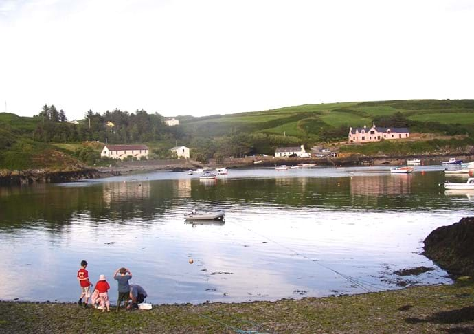 Foreground shows the small pebble beach nearby, Mill Cove pier in the background.