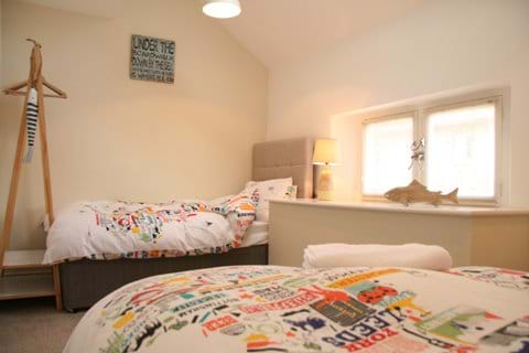 Light and airy twin bedroom with soft feather duvets and pillows to relax and unwind in