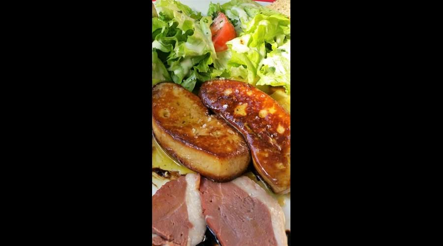 Slices of pan cooked fois gras on a plate with lettuce and slices of duck