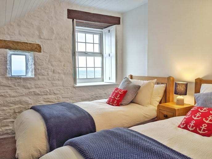 The second bedroom has twin oak beds and a spectacular sea view