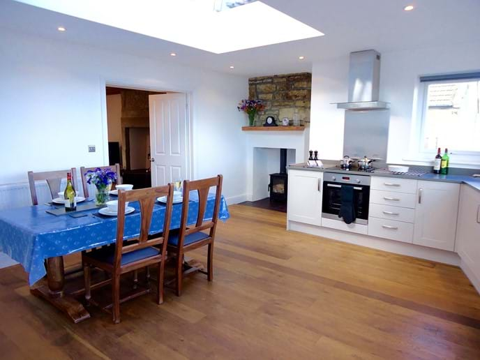 The kitchen is fully equipped with fridge, freezer, dishwasher, washing machine and tumble dryer. It even has its own log burner. Double doors lead through to the living room