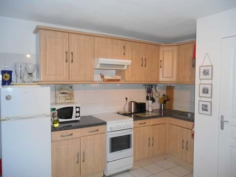 Kitchen with fridge/freezer, gas/electric over and hob, microwave, washing machine