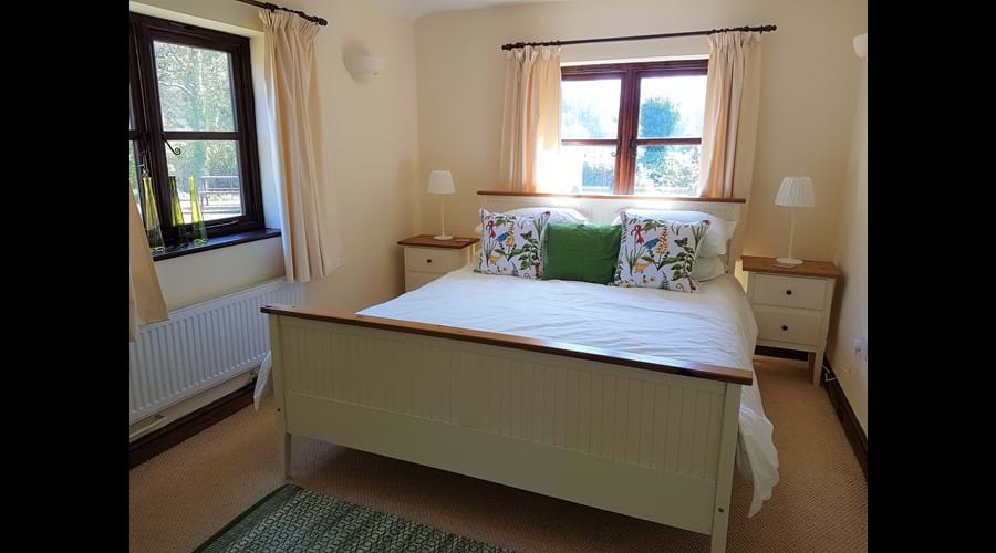 Bright, airy King Sized bedroom with garden views from both windows.
