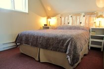 The second bedroom located on the top floor in the main cottage is furnished with a comfortable queen-sized bed.