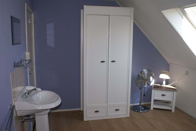 One of the twin bedrooms with a basin and wardrobe