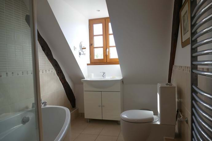 This bathroom has a bath with shower over